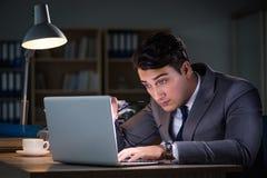 Der Mann, der im Büro für Überstunden bleibt Lizenzfreies Stockbild