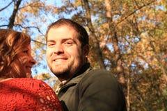 Der Mann, der Kamera als Frau betrachtet, lächelt an ihm mit blauem Herbsthimmel Stockbild