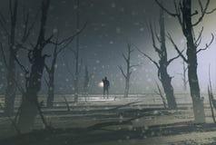 Der Mann, der Laterne hält, steht im dunklen Wald mit Nebel Stockbilder
