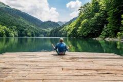 Der Mann, der in Lotussitz auf Biogradsko See im n meditiert lizenzfreie stockfotografie