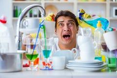 Der Mann, der am Müssen Teller waschen frustriert ist lizenzfreie stockfotos