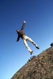 Der Mann, der mit den breiten Armen springt, öffnen sich Stockbild