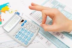 Der Mann, der O.K. darstellt, unterzeichnen über 1040 US-Steuerformular - konzentrieren Sie sich auf Taschenrechner Stockfotos