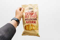 Der Mann, der organische Biowindung Trafa hält, schnitt Chips Stockfotos