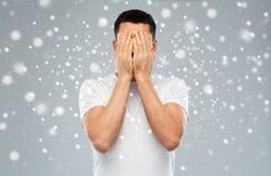 Der Mann, der sein Gesicht mit bedeckt, überreicht Schnee Lizenzfreies Stockfoto