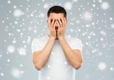 Der Mann, der sein Gesicht mit bedeckt, überreicht Schnee Stockfotos