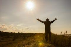 Der Mann, der seine Hände anhebt, up Schattenbildhintergrund Stockfotos