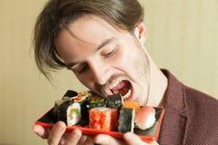 Der Mann, der versucht, Sushi zu essen, stellte ohne Hände ein Lizenzfreie Stockfotografie