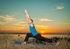 Der Mann, der Yoga macht, trainiert draußen Stockfotografie