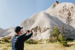 Der Mann in der dunklen Kleidung macht Foto von schönen Felsen auf Smartphone am warmen sonnigen Tag in Cappadocia in der Türkei Lizenzfreies Stockbild