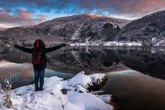Der Mann, der durch die Schönheit von See aufgeregt werden und die Berge gestalten im Winter an der Dämmerung landschaftlich stockbild