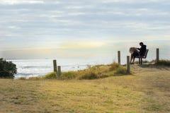 Der Mann, der durch Morgensonne silhouteed ist, sitzt, die Bucht von viel-Zeiten lesend stockfotografie