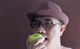 Der Mann in einem braunen Hut und in grünen Gläsern isst einen grünen Apfel an Stockfoto