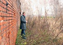 Der Mann in einem Mantel über eine Wand Lizenzfreies Stockbild