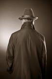 Der Mann in einem Regenmantel und in einem Hut Lizenzfreie Stockfotografie