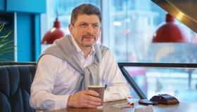 Der Mann, der in einem weißen Hemd mit Strickjacke reif ist, hält Morgenkaffee Stockfotografie