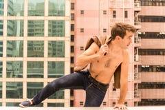 Der Mann einen Kragstein einer Dachspitze springend Lizenzfreie Stockfotos