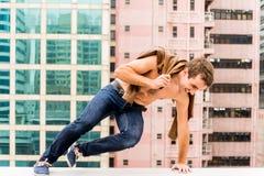 Der Mann einen Kragstein einer Dachspitze springend Lizenzfreies Stockfoto