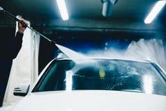 Der Mann, der einen Waschanlageabschluß herauf Auto bearbeitet, säubert stockfotos