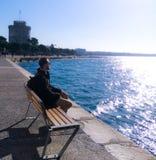 Der Mann, der in einer Bank im Meer sitzt, bewundert die Ansicht schaut ruhig und ruhig stockbild