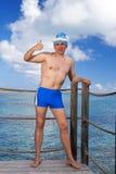 Der Mann in einer Kappe des Badeanzugs und des Sankt-Klaus des neuen Jahres Lizenzfreie Stockbilder