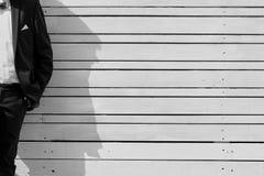 Der Mann in einer Klage an einem Bretterzaun lizenzfreie stockfotos