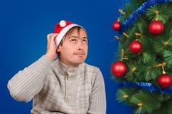 Der Mann in einer roten Kappe verkratzt einen Nacken, der nahe einem grünen Tannenbaum sitzt Stockbild