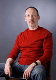 Der Mann in einer roten Strickjacke Stockfotos