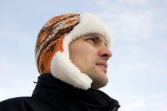 Der Mann in einer Winterschutzkappe Lizenzfreie Stockfotos