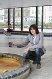 Der Mann füllt einen Becher mit Mineralwasser Stockbild