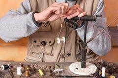Der Mann, der Forelle macht, fliegt Fliegen Sie, Ausrüstung und Material für Fliegenfischereivorbereitung binden stockbilder
