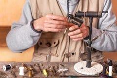 Der Mann, der Forelle macht, fliegt Fliegen Sie, Ausrüstung und Material für Fliegenfischereivorbereitung binden lizenzfreie stockbilder