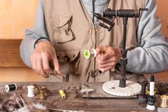 Der Mann, der Forelle macht, fliegt Fliegen Sie, Ausrüstung und Material für Fliegenfischereivorbereitung binden lizenzfreie stockfotos