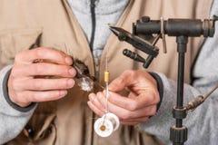 Der Mann, der Forelle macht, fliegt Fliegen Sie, Ausrüstung und Material für Fliegenfischereivorbereitung binden stockfoto