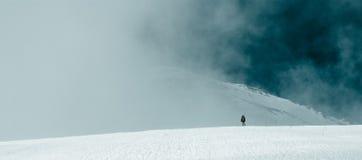 Der Mann am Fuß einer Bergspitze in den Wolken Stockfotos