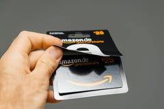 Der Mann, der gegen grauen Hintergrund 25 Euros Amazon-Gutschein hält, ist Lizenzfreies Stockbild