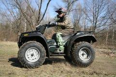 Der Mann geht auf ATV im Früjahr Stockfotos