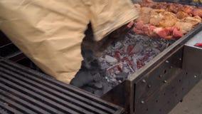 Der Mann gießt Kohle in den Messingarbeiter stock video