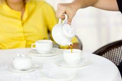 Der Mann gießt Tee in der Schale Stockbilder