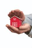 Der Mann hält das rote Haus in einer Hand an Lizenzfreie Stockfotografie