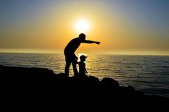 Der Mann hält die Kind-` s Hand und die Punkte mit seiner zweiten Hand zum Horizont Stockfoto