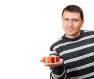 Der Mann hält an die Palme ein kleines rotes Geschenk Stockbilder