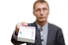 Der Mann hält heraus ein Bündel Anmerkungen 500 Euros Stockfoto