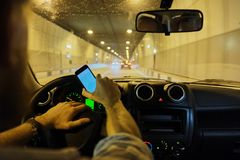 Der Mann der Hand unter Verwendung des Smartphone beim Fahren des selektiven Fokus des Autos - Transport- und Fahrzeugkonzeptauto stockfoto