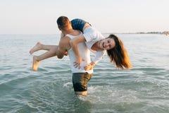 Der Mann hat das Mädchen auf einer Schulter angehoben Lizenzfreies Stockfoto