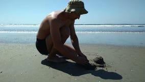 Der Mann, der heraus, zusammenstoßendes Sandburg versucht er ausflippt, auf dem Strand zu errichten Wut im ungewöhnlichen inviron stock footage