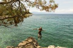 Der Mann herein springend zum Meer Stockfotografie