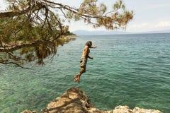 Der Mann herein springend zum Meer Stockfoto