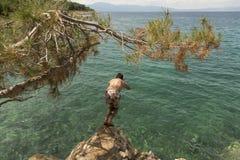 Der Mann herein springend zum Meer Lizenzfreie Stockfotos