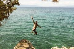 Der Mann herein springend zum Meer Lizenzfreies Stockfoto